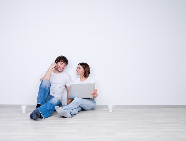 Het mooie glimlachende paar ontspant in de lege ruimte met laptop