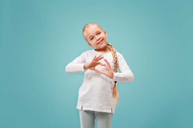 Het mooie glimlachende tienermeisje maakt de vorm van een hart met haar handen op het blauw