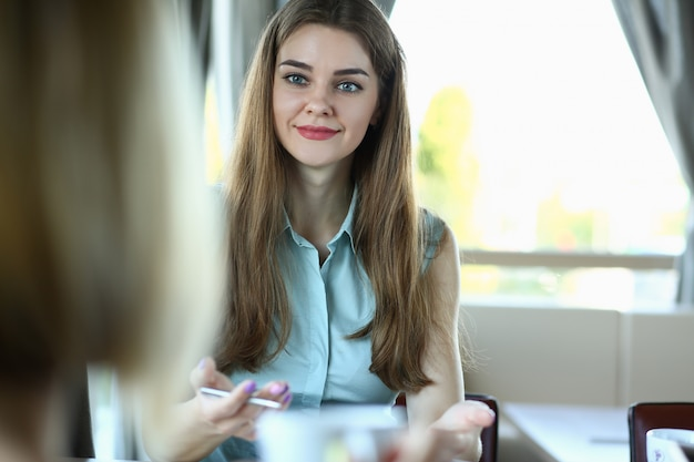 Het mooie glimlachende vrolijke meisje bij koffie ziet eruit