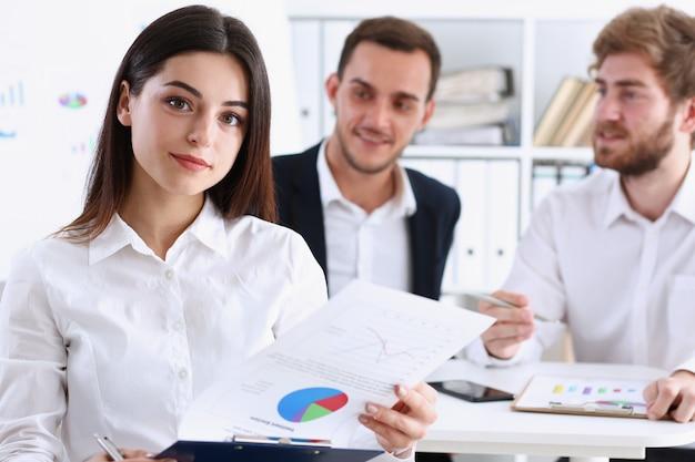 Het mooie glimlachende vrolijke meisje op het werk kijkt in camera met collega sgroep op achtergrond. administratieve arbeider bij van de de aanbiedings moderne levensstijl van de werkruimtebaan het concept van de het beroepstrein van de cliëntbezoek