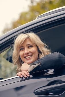 Het mooie glimlachende vrouw stellen in autoraam