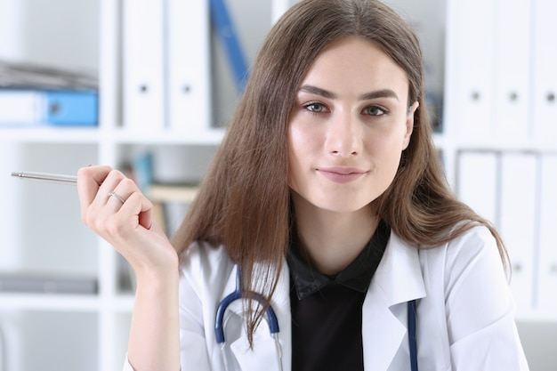 Het mooie glimlachende vrouwelijke klembord van de artsenholding