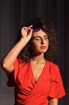 Het mooie, goed verzorgde meisje in een rode jurk en bril. groot portret