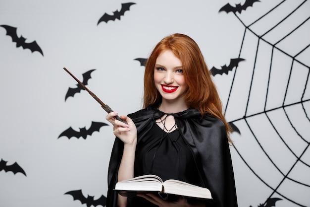 Het mooie heks spelen met magische stok en magisch boek op grijze achtergrond.