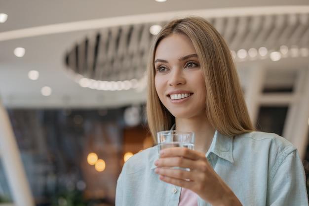 Het mooie het glimlachen glas van de vrouwenholding met zoet water. dieet, gewichtsverlies, gezonde levensstijl concept