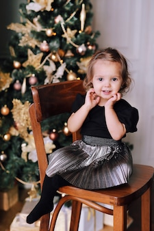 Het mooie het glimlachen meisje spelen dichtbij kerstboom thuis