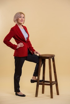 Het mooie hogere vrouw stellen op stoel