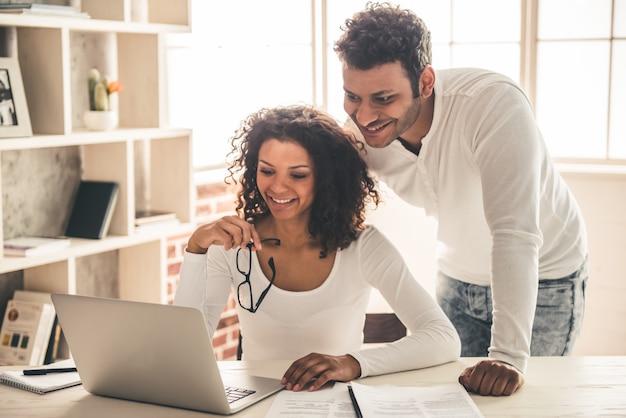 Het mooie jonge afro-amerikaanse paar gebruikt laptop