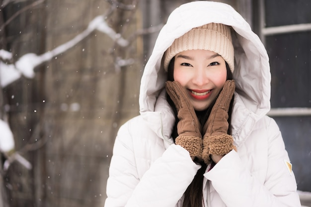Het mooie jonge aziatische vrouw glimlachen gelukkig voor reis in sneeuw wintertijd
