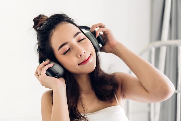 Het mooie jonge aziatische vrouw ontspannen die thuis aan muziek met hoofdtelefoons op bed luisteren
