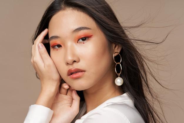 Het mooie jonge aziatische vrouw stellen in modieuze kleren