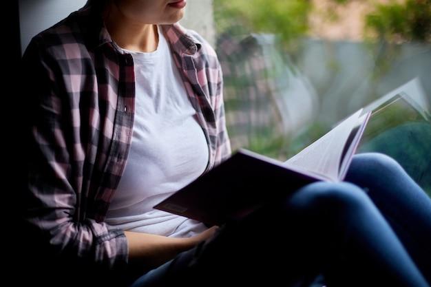 Het mooie jonge boek van de vrouwenlezing dichtbij venster thuis.