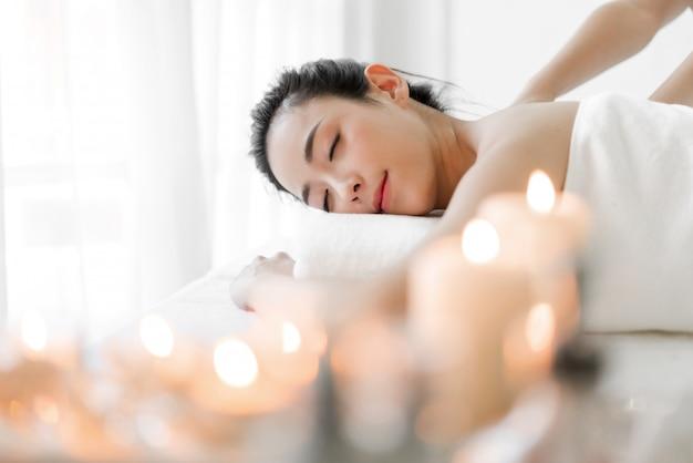 Het mooie jonge de huidbehandeling van de vrouwenschoonheid ontspannen liggend op handdoek in het masseren en kuuroordsalon
