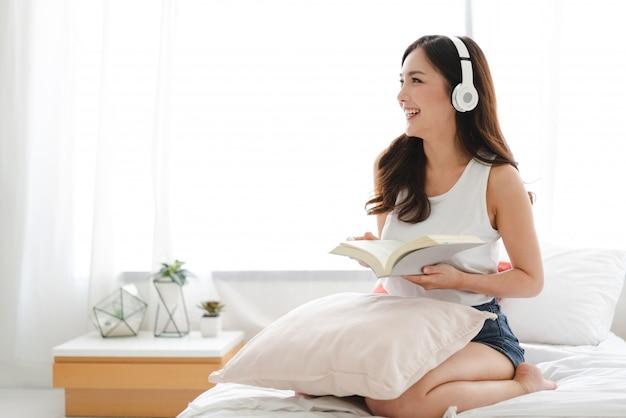Het mooie jonge de vrouw van azië ontspannen die thuis aan muziek met hoofdtelefoons op bed luisteren