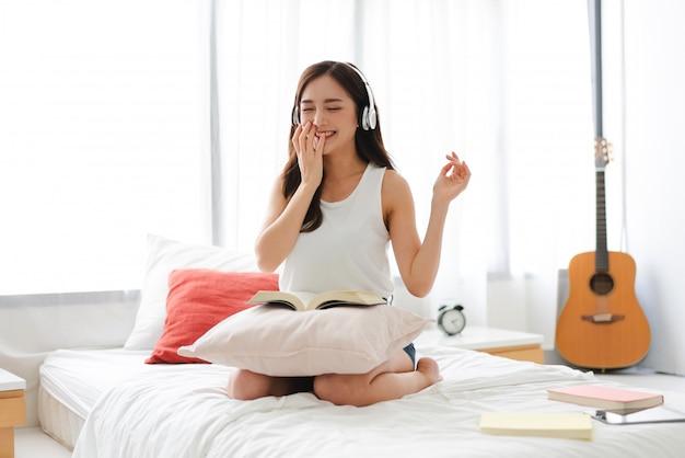 Het mooie jonge de vrouw van azië ontspannen thuis luisteren aan muziek met hoofdtelefoons op bed