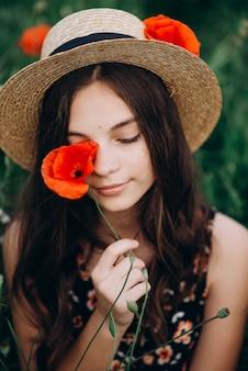 Het mooie jonge donkerbruine meisje in een hoed in een gebiedsgras sluit één oog met een rode papaverbloem. close-up portret van een meisje.