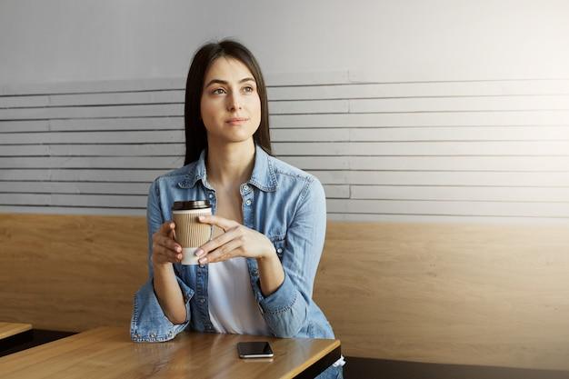 Het mooie jonge donkerharige meisje in denimoverhemd en wit t-shirt drinkt koffie, kijkend opzij met ontspannen uitdrukking en wachtende vriend die laat zijn.