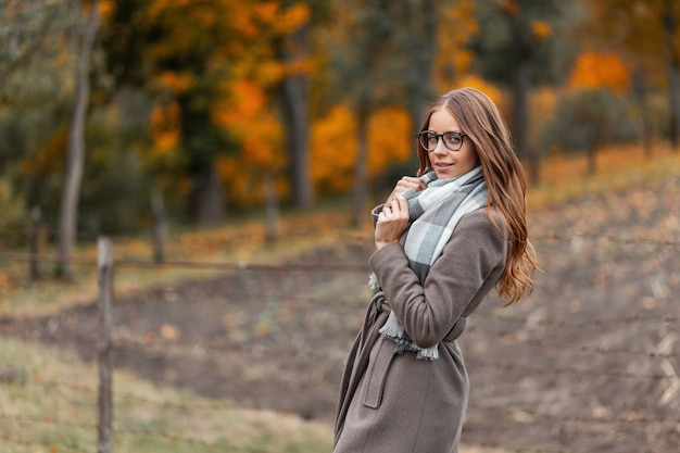 Het mooie jonge gelukkige vrouwenmodel met bril in een lange jas in een gebreide vintage sjaal geniet van rust in het herfstpark met bomen met oranje gebladerte. blij meisje staat in het veld en glimlacht.