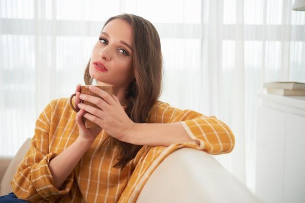 Het mooie jonge kaukasische vrouw stellen op laag thuis met kop thee