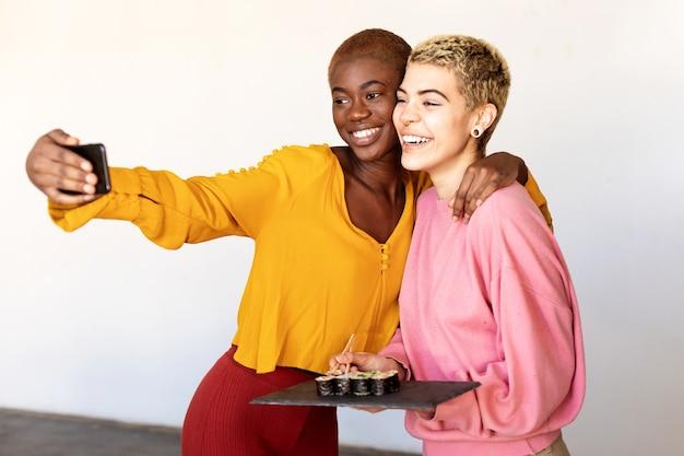 Het mooie jonge lesbische paar doet selfie met behulp van een slimme telefoon en lacht terwijl ze een sushiplaat vasthoudt