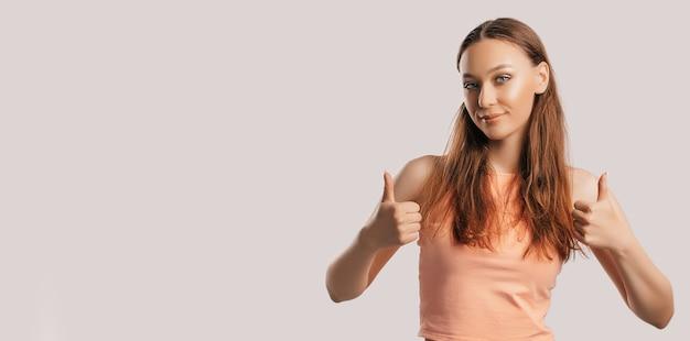 Het mooie jonge meisje glimlacht en toont duimen omhoog gebaar met twee handen op een witte geïsoleerde achtergrond. positieve vrouw wijst naar een idee, een plek voor reclame