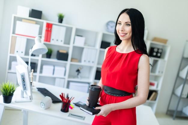Het mooie jonge meisje in een rood kostuum bevindt zich in het bureau en houdt een notitieboekje en een glas koffie.
