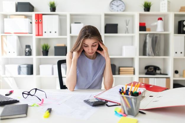 Het mooie jonge meisje in het kantoor zit aan de tafel en houdt haar handen achter haar hoofd.