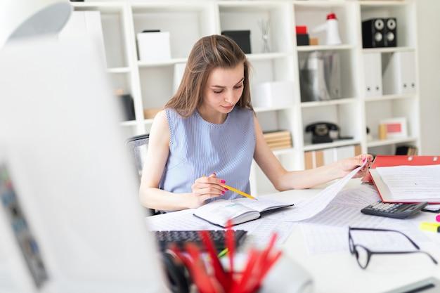 Het mooie jonge meisje in het kantoor zit aan een tafel en werkt met een potlood, blocnote en documenten.