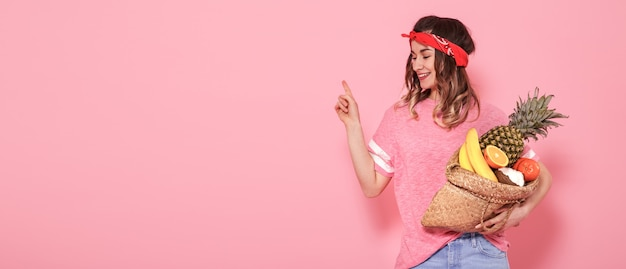 Het mooie jonge meisje in roze t-shirt, houdt een volledige strozak fruit op roze achtergrond