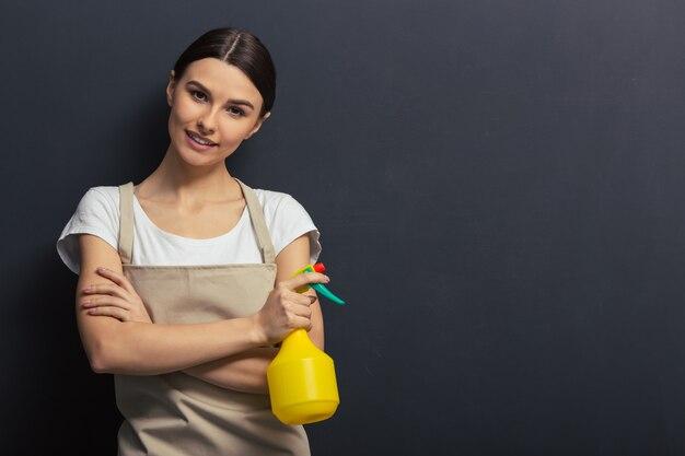 Het mooie jonge meisje in schort houdt een spuitbus. copyspace-achtergrond voor het schoonmaken van concept