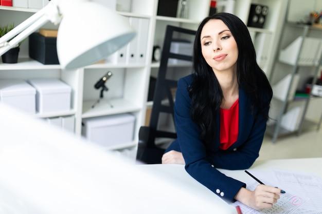 Het mooie jonge meisje kijkt door documenten, zittend in het kantoor aan de tafel.