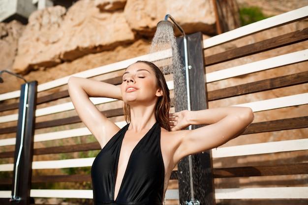 Het mooie jonge meisje kleedde zich in swimwear het nemen van een douche op strand