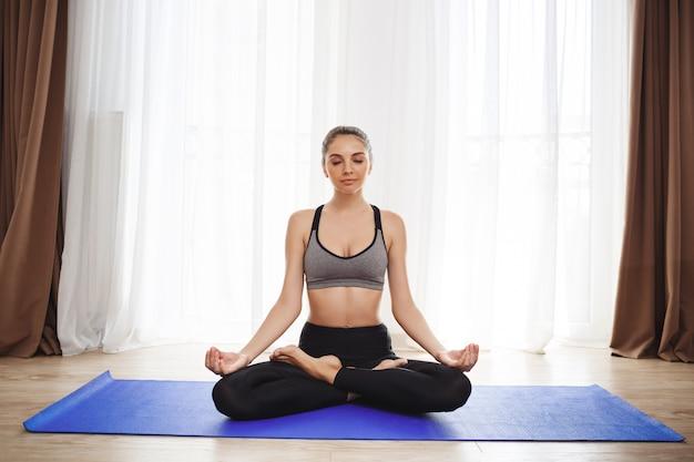 Het mooie jonge meisje maakt yogaoefeningen op vloer