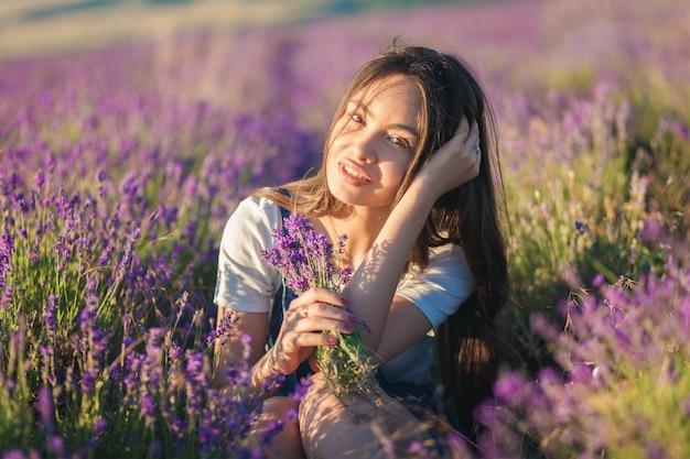 Het mooie jonge meisje met een boeket van bloemen zit op een lavendelgebied in het zonlicht