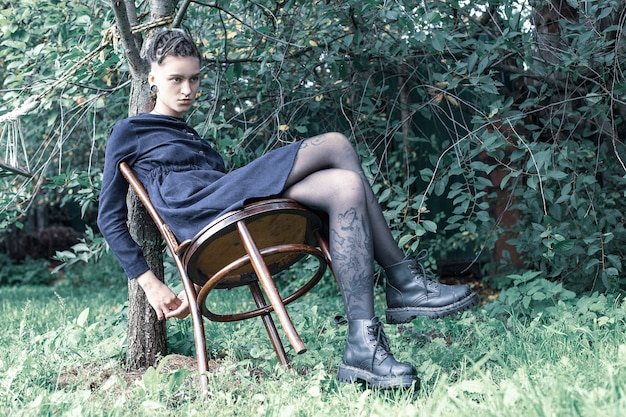 Het mooie jonge meisje met een ongewoon uiterlijk zit op een stoel onder een appelboom.