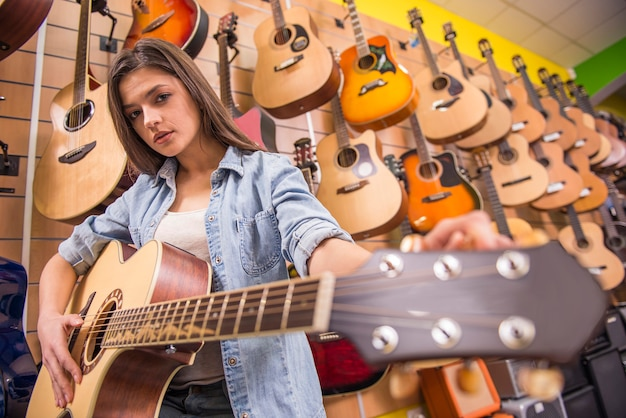 Het mooie jonge meisje speelt gitaar in een muziekopslag.