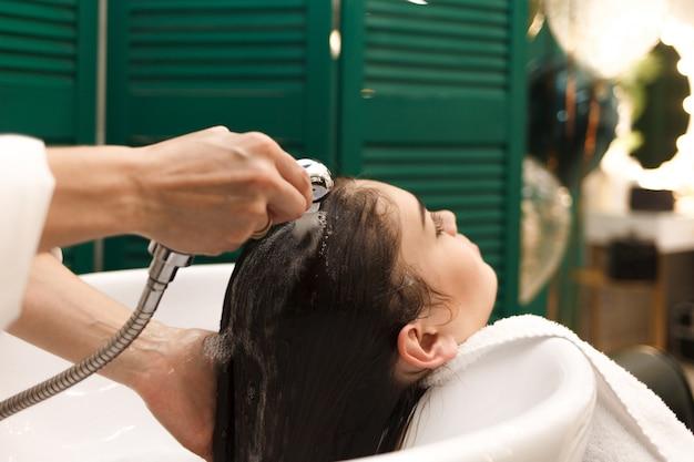 Het mooie jonge meisje wast haar hoofd in een schoonheid. kapper wast haar voor cliënt