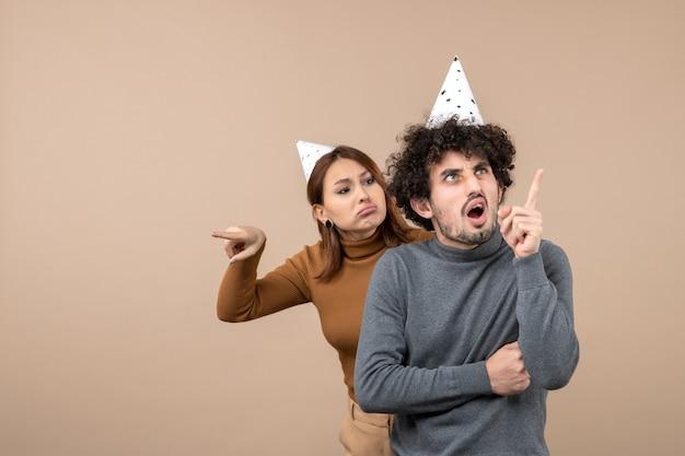 Het mooie jonge paar draagt de boze meid van het nieuwjaarshoed die iets bekijkt dat zich achter kerel bevindt die hierboven op grijs richt
