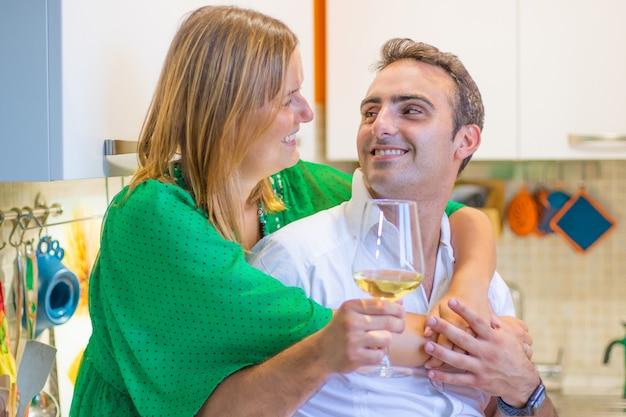 Het mooie jonge paar drinkt thuis wijn en glimlacht in keuken