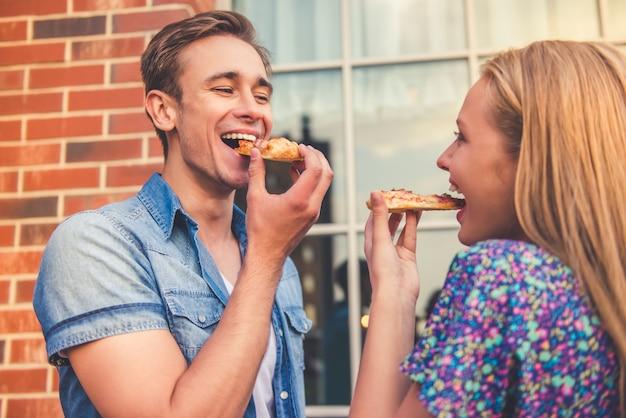 Het mooie jonge paar eet pizza