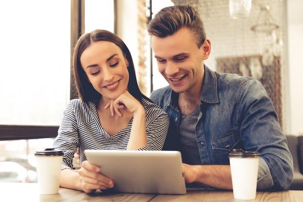 Het mooie jonge paar gebruikt een digitale tablet en glimlacht