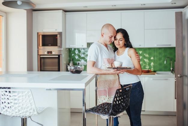 Het mooie jonge paar grafeerde glimlachend terwijl thuis het koken in de keuken.