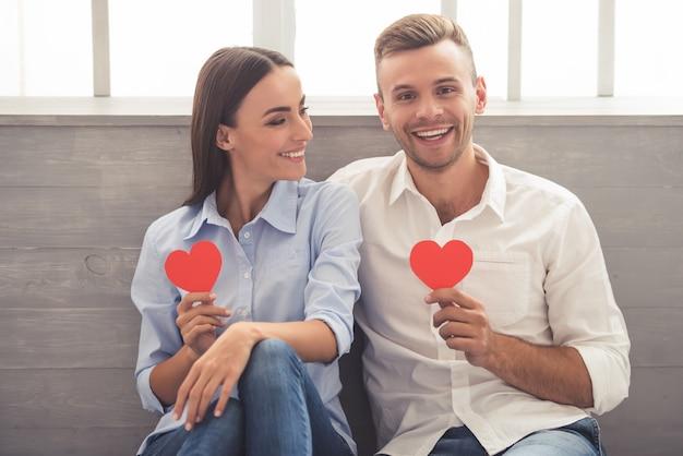 Het mooie jonge paar houdt kleine document harten