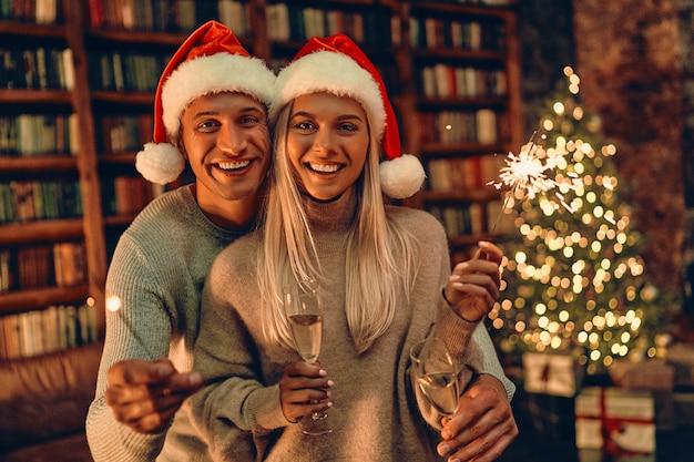 Het mooie jonge paar in kerstmanhoeden houdt glazen champagne en glimlacht terwijl thuis nieuwjaar viert.