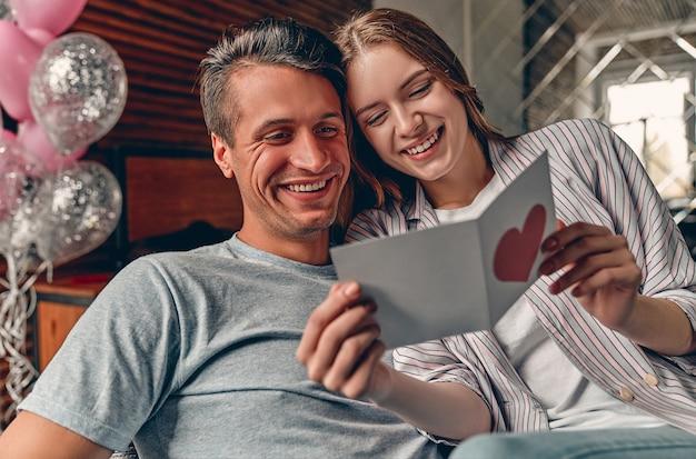 Het mooie jonge paar in slaapkamer gelezen valentijnskaartkaart.
