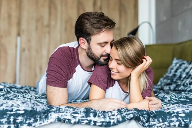 Het mooie jonge paar in slaapkamer ligt op bed. samen tijd doorbrengen.