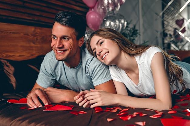 Het mooie jonge paar in slaapkamer ligt op het bed