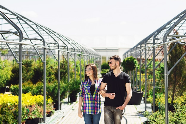 Het mooie jonge paar in vrijetijdskleding kiest installaties en het glimlachen