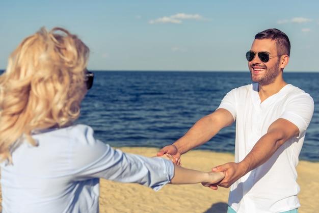 Het mooie jonge paar in zonglazen houdt handen.