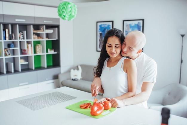 Het mooie jonge paar maalt samen groenten in de keuken.